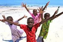 Manos sacerdotales que acompañan y cuidan a los niños en su visita al mar.