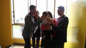 Padres y padrinos en el momento de signar en la frente a Samuel Esteban