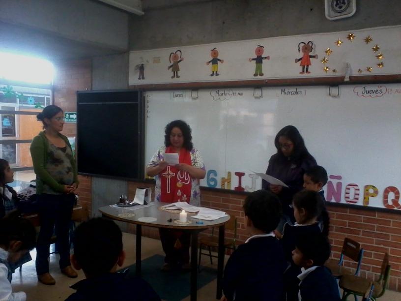 Teachers, children and the Rev. Aida celebrating the Eucharist.
