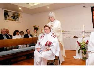 La obispa co-celebrante Dana Sibyl Reynolds imponiendo las manos.