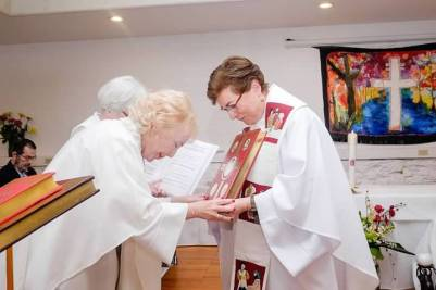 La Obispa Bridget Mary Meehan hace entrega del Libro del Altar.